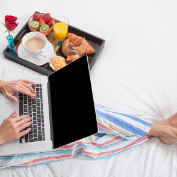 Woman in pajamas typing on laptop with breakfast on tray